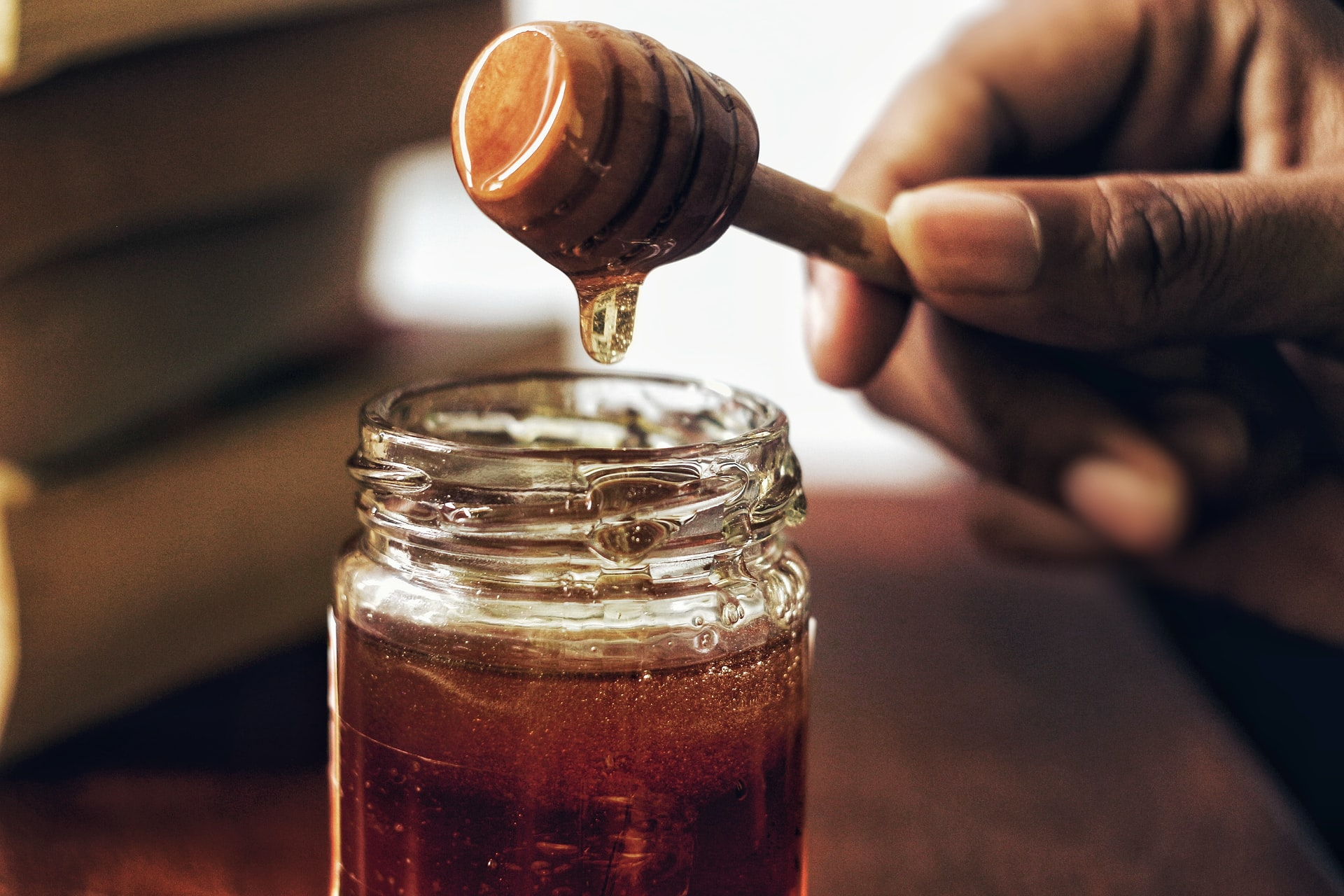 Honey dripping in jar